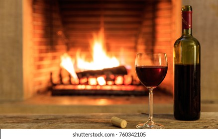 A glass and a bottle of red wine on a wooden table, blur burning fireplace background