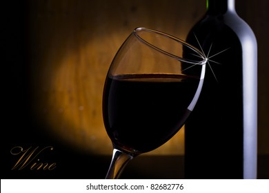 Glass and a bottle of red wine on a wooden background