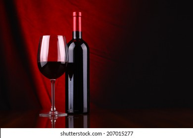 Glass and bottle of red wine over a draped background lit red