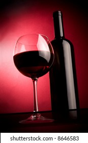 a glass and a bottle of red wine in the spotlight