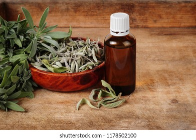glass bottle with sage oil, dried and fresh sage over wooden background