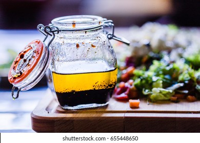 A Glass Bottle with Salad Dressing consisting of Balsamic Vinegar, Olive Oil, Pepper and Salt, Salad on the Background, Horizontal View