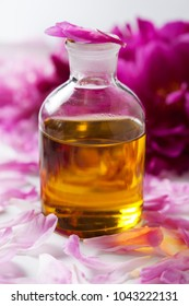 Glass bottle of scented oil with rose petals