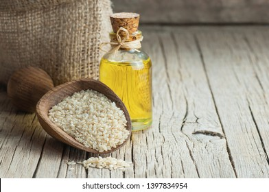 Glass bottle of sesame oil and raw sesame seeds in wooden shovel with burlap sack on wooden table. Uncooked sesame background concept with copy space