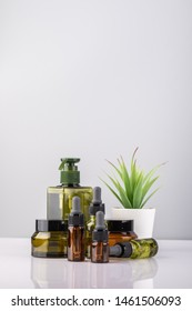 Glass bottle and soap dispenser on grey background