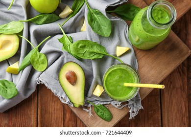 Glass and bottle of spinach smoothie on wooden table