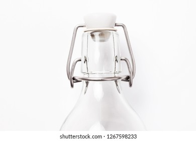 Glass bottle top with plastic cap and metal lever lid isolated on white. Home beer brewing equipment.