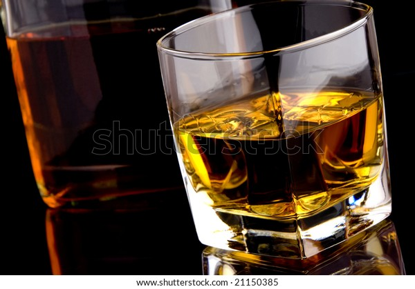 a glass and bottle of whiskey