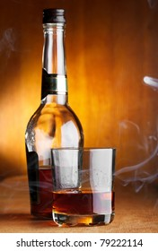 glass and bottle of whiskey with smoke