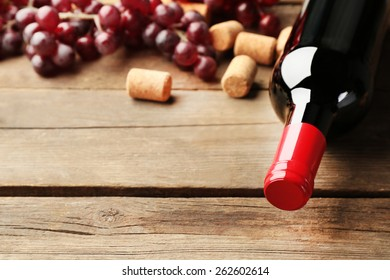 Glass bottle of wine with corks and grapes on wooden table background