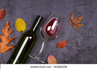 Glass and bottle of wine, grape and bread on gray stone texture background. View from above, top studio shot