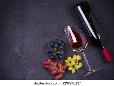 Glass and bottle of wine with grapes, figs and nuts on black stone texture background. View from above, top studio shot