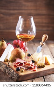 glass and bottle of wine with jamon, cheese, pears and grapes