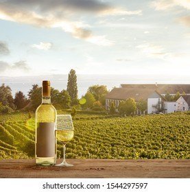 Glass and bottle of wine on wooden rail with country rural scene in background. Green leaves and calm summer sunshine day. Copyspace. Alcohol drinks on backyard of big house.