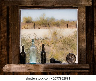 Glass Bottles and an Antique Alarm Clock framed in a Rustic Wooden Window overlooking the desert