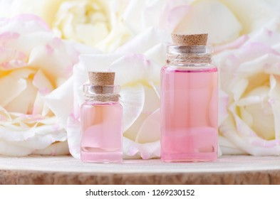 glass bottles of aroma oil and fresh rose flowers, selective focus