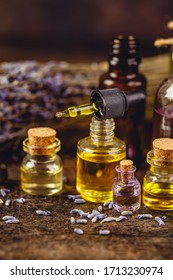 Glass bottles aroma oil, zen stones and dry lavender flowers on wooden table. Spa Treatment