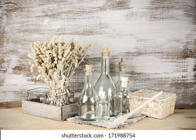 Glass bottles and dry flowers on rustic wooden background.