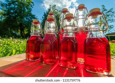 glass bottles of homemade cherry juice in the summer sun