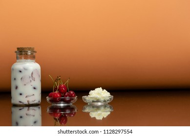 glass bottles with a homemade cherry smoothie with kefir yogurt, a glass plate with kefir grains, a plate with red cherries and surface reflection, peach background