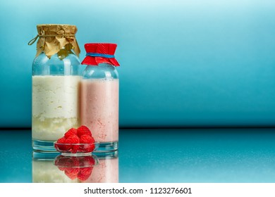 glass bottles with a homemade raspberry smoothie with kefir yogurt, regular kefir yogurt, a plate with raspberry and surface reflection, blue background