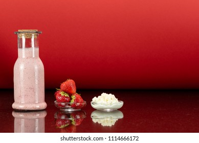 glass bottles with a homemade strawberry smoothie with kefir yogurt, a glass plate with kefir grains, a plate with strawberry and surface reflection, red background