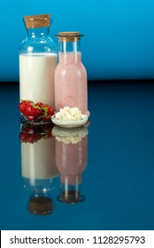 glass bottles with a homemade strawberry smoothie with kefir yogurt, fresh milk, a glass plate with kefir grains, a plate with strawberry and surface reflection, blue background