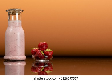 glass bottles with a homemade strawberry smoothie with kefir yogurt, a plate with strawberry and surface reflection, peach orange background