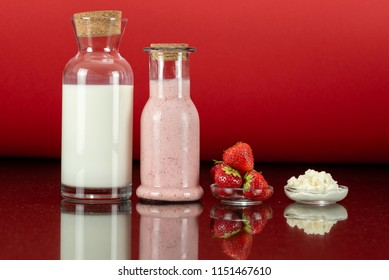 glass bottles with a homemade strawberry smoothie with kefir yogurt, fresh milk, a glass plate with kefir grains, a plate with strawberry and surface reflection, red background