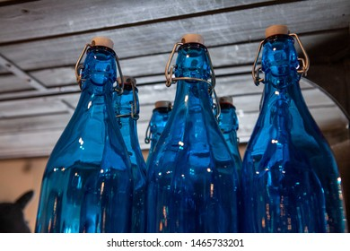 Glass bottles in homeware shop. Decorative blue glass bottles are seen up close, on a shelf inside an environmentally friendly local homeware store, ornamental glassware for sale