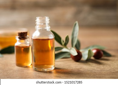 Glass bottles with jojoba oil on wooden table. Space for text
