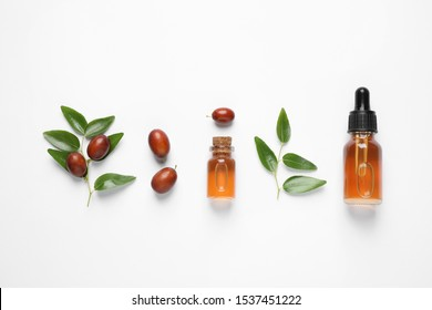 Glass bottles with jojoba oil and seeds on white background, top view