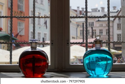 Glass bottles in the pharmacy in Tallinn. Town Hall Square, through the prism of a glass jar with red and blue medicine in the Town Hall pharmacy. Tallin, Estonia.