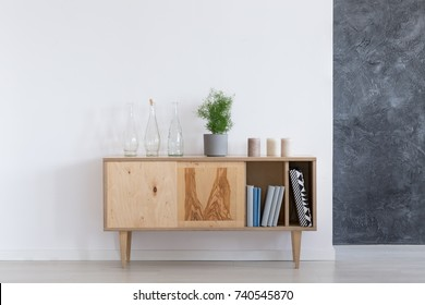 Glass bottles, plant in grey pot and candles on vintage wooden cupboard against a white wall