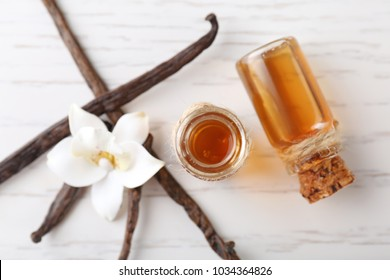 Glass bottles with vanilla extract on wooden table, top view