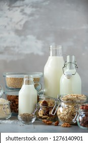 Glass bottles of vegan plant milk and almonds, nuts, coconut, hemp seed milk on grey concrete background. Banner with copy space. Dairy free milk substitute drinks and ingredients.