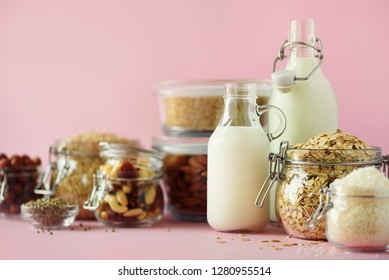 Glass bottles of vegan plant milk and almonds, nuts, coconut, hemp seed milk on pink background. Banner with copy space. Dairy free milk substitute drinks and ingredients