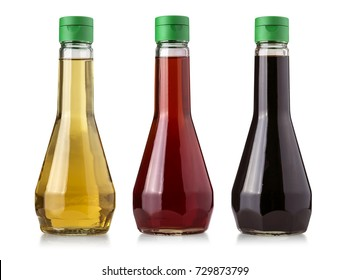 Glass bottles of vinegar isolated on white background