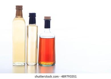 Glass bottles of vinegar on white background