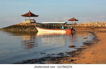 Glass Bottom Tourist Reef Viewing Boat  and reflections at dawn on Sanur beach, Bali, Indonesia.