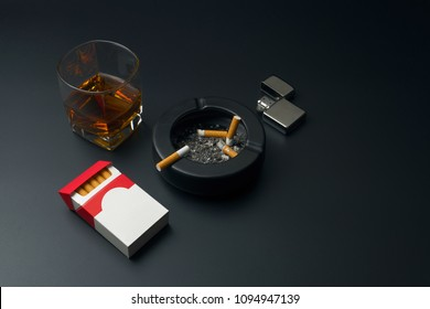 a glass of bourbon whiskey, cigarette pack, chrome lighter and black ceramic ashtray full of ashes with the cigarette butt, on the black table