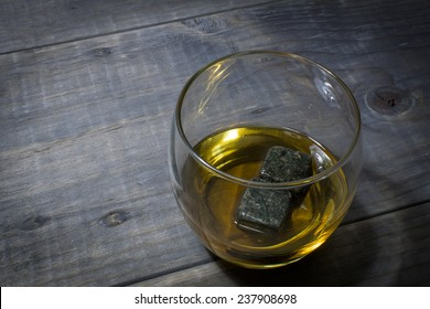 Glass of Bourbon with Whisky Stones on a Vintage Wood Farm Table