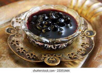 A glass bowl of blueberry jam
