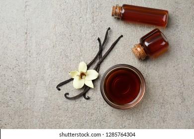 Glasschüssel und Flaschen mit Vanilleextrakt auf grauem Hintergrund