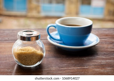 Glass bowl container of brown sugar on a wooden table, cup of coffee in the background.