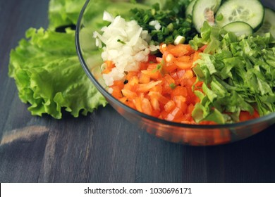 Glass bowl with cutted vegetables for a salad. Close up. Bell pepper, onion, leafy greens and cucumbers cutted in pieces. Wooden background.