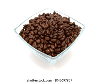 Glass bowl filled to the brim with dark roasted coffee beans, on a white background