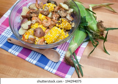 A glass bowl is filled with corn on the cob, red potatoes, and shrimp - a classic shrimp boil.
