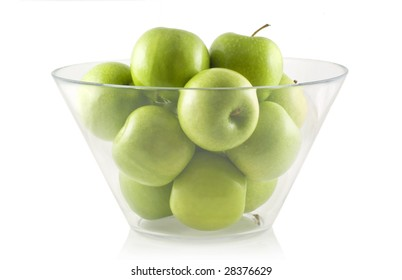 Glass bowl filled with green apples, isolated on white.