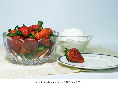 A glass bowl filled with strawberries and beside that is a bowl of whipped cream also a plate with one strawberry on it.